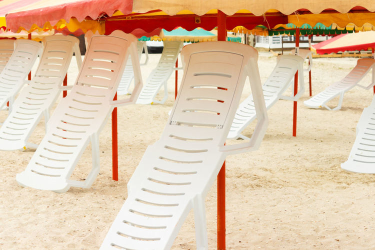 Row of chairs on sand at beach