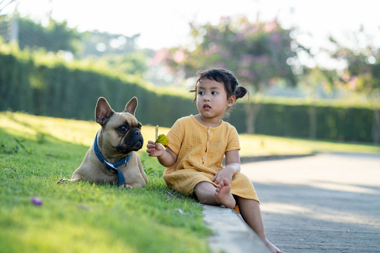 Portrait of a boy with dog sitting outdoors