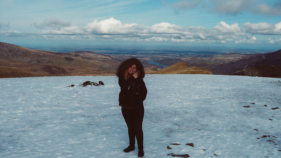 Full length of young woman standing on mountain against sky