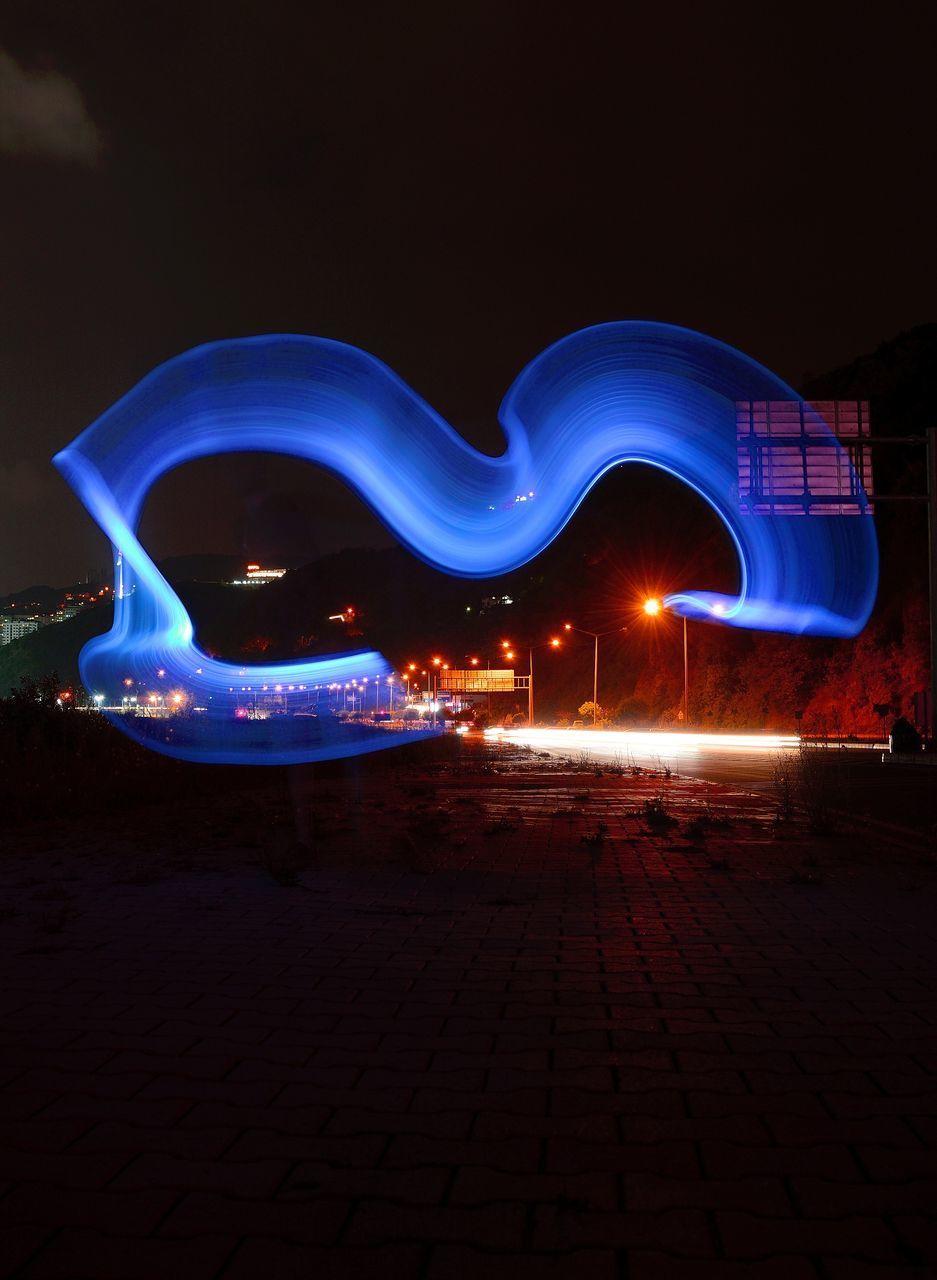 ILLUMINATED LIGHT TRAILS ON CITY STREET AT NIGHT
