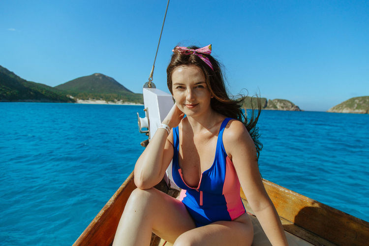 Portrait of woman sitting on boat in sea against clear sky
