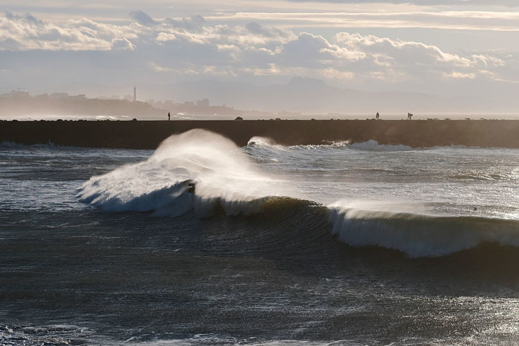 Sea waves splashing on shore against sky during sunset