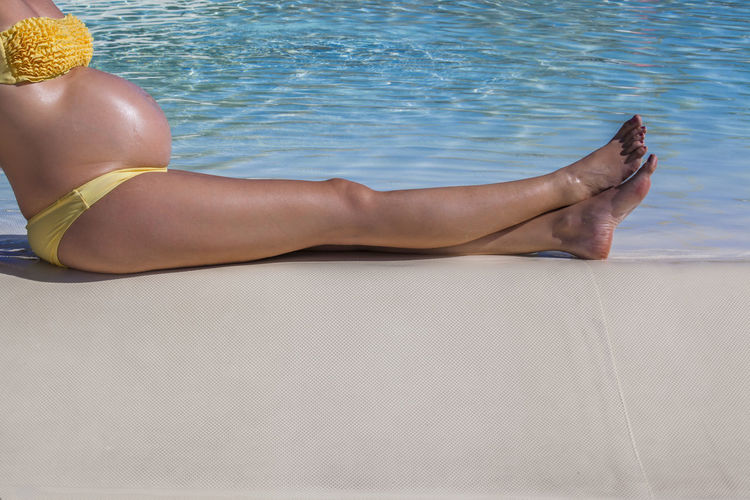 Low section of woman relaxing on swimming pool
