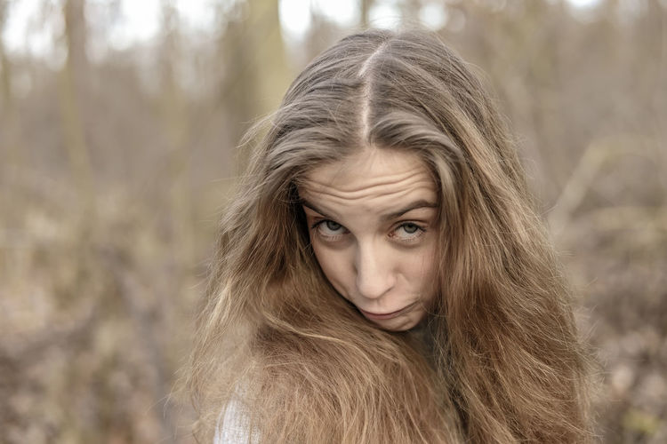 Close-up portrait of teenage girl in forest