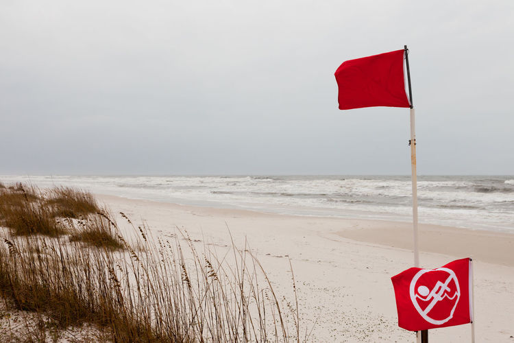 Red flags on a Gulf Coast Beach signal swimming in ocean prohibited due to dangerous surf, undercurrent and storm conditions Gulf Coast Beach Beach Sand Beach Flags Flags In The Wind  Storm Stormy Weather Stormy Stormy Sea Sea Ocean Red Flags Danger Dangerous No Swimming No Swimming Sign No Swimming Allowed Wind Windy Surf Waves Coast Coastal Landscape Red Water Nature Horizon Horizon Over Water Communication Warning Sign Sign Sand Scenics - Nature No People Outdoors
