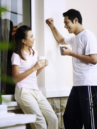 Couple talking while having coffee against wall