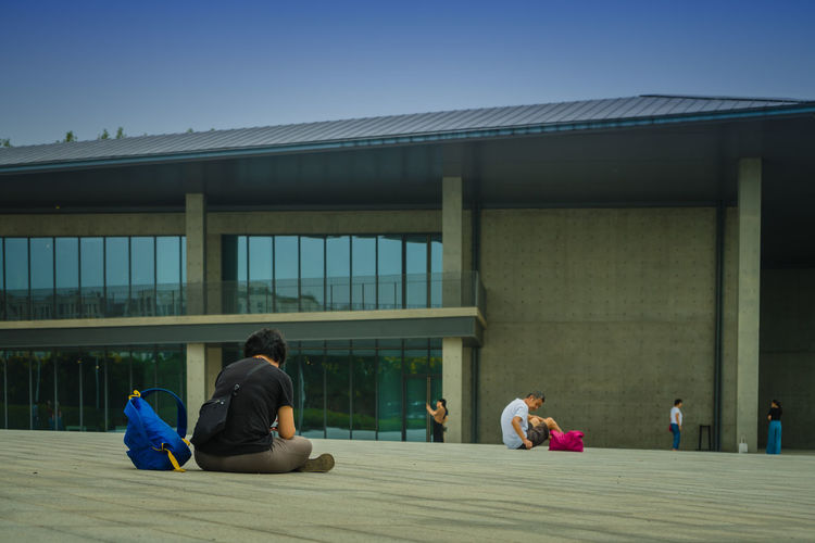 People sitting on built structure against clear blue sky