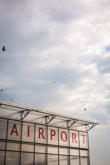 Low angle view of airport against  cloudy sky