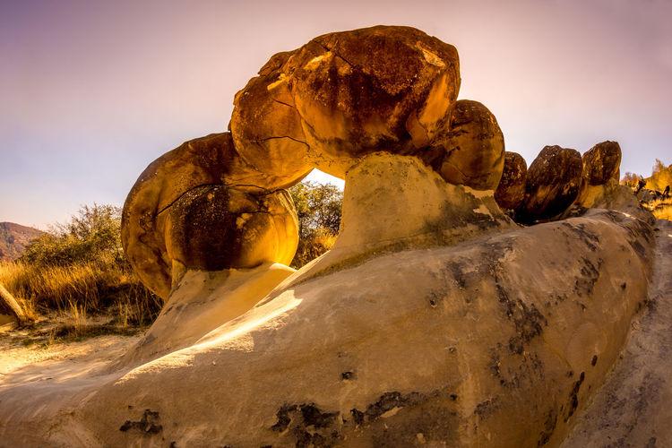 Rock formation on rocks against sky during sunset