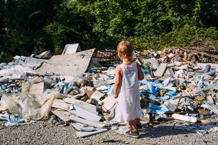 Little girl at a dump among a heap of scattered garbage in the forest.