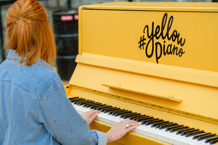 Rear view of woman playing piano outdoors
