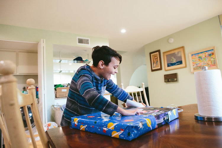 Man using mobile phone while sitting on table at home