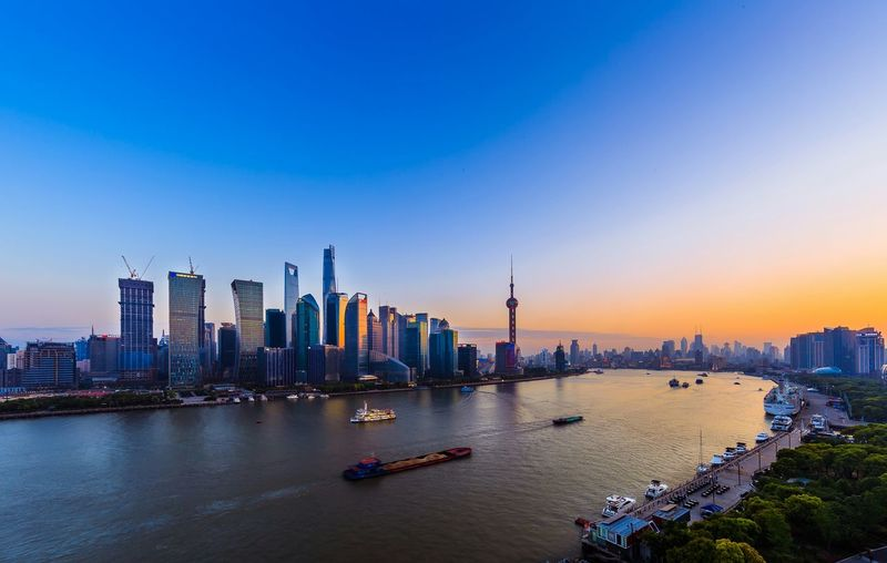 Huangpu River By Cityscape Against Blue Sky During Sunset