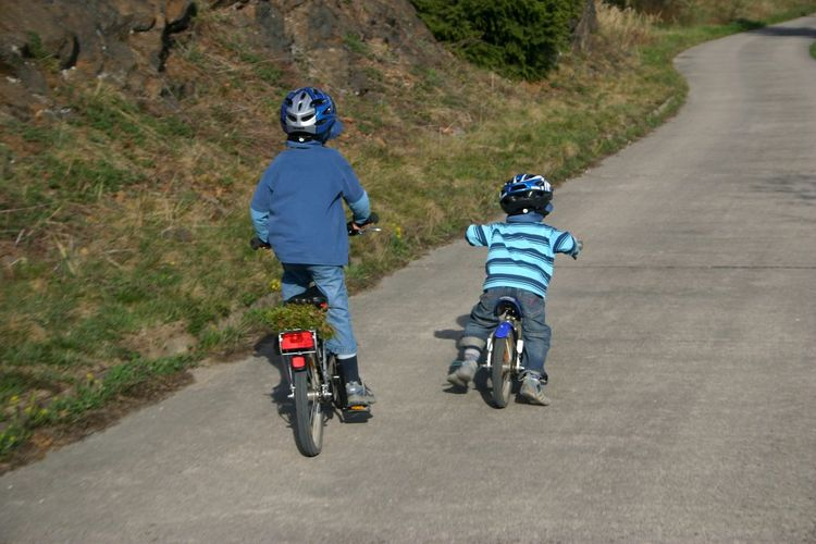 Rear View Of Siblings Cycling On Road