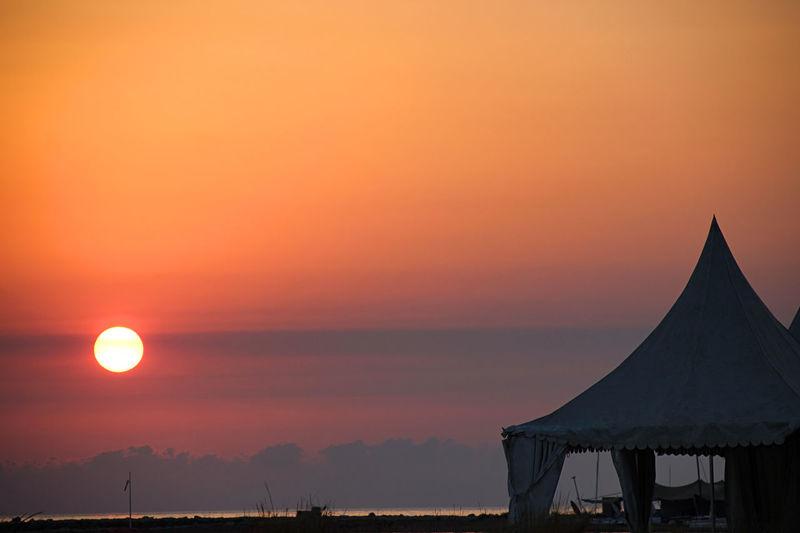 Silhouette tent at beach against orange sun in romantic sky