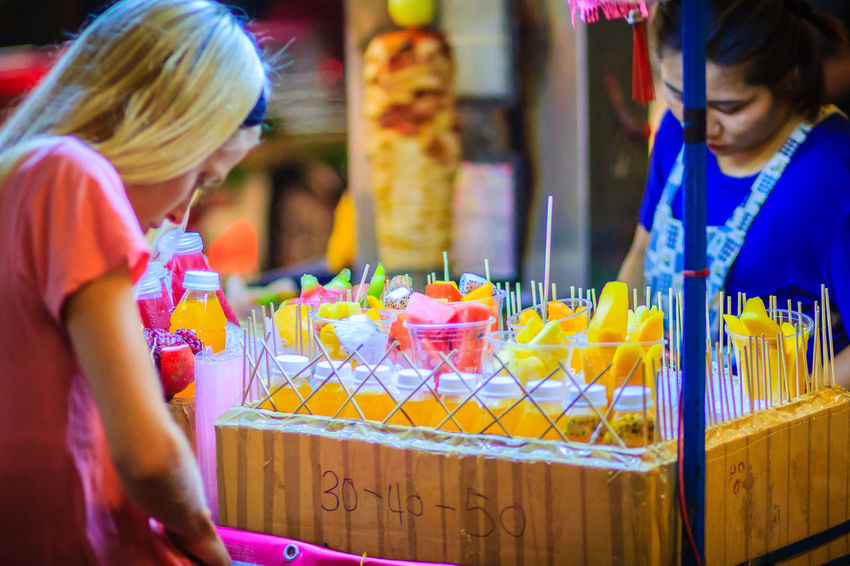 Bangkok, Thailand - March 2, 2017: Unidentified tourist is buying sliced fruits that arranged in plastic cup from street food vendor at Khao San Road night market, Bangkok, Thailand. Khao San Rd Khao San Road KhaoSan Khaosan Rd. Khaosandroad Khao San Khao San Knok Wua Khao San Rd. Khaosan Road Khaosanroad Night Market Night Market In Thailand