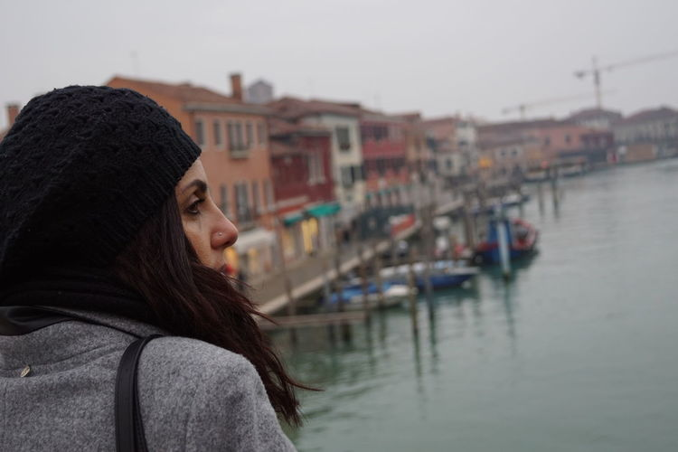 Beautiful woman standing by canal and buildings in city