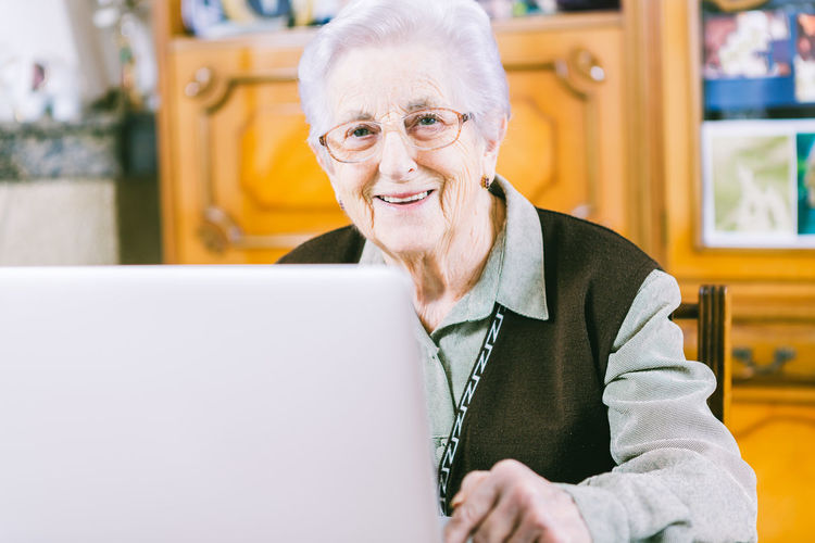 Senior woman surfing the net with a laptop at home. At Home Adult Adults Only Cheerful Communication Computer Connection Day Eyeglasses  Happiness Indoors  Laptop One Person People Retirement Senior Adult Senior Women Sitting Smiling Table Technology Using Laptop Wireless Technology