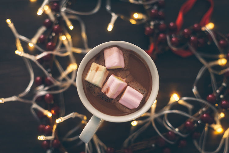 Close-Up Of Marshmallows In Coffees On Table Surrounded With Lighting