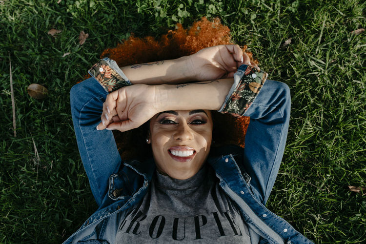 Portrait of a smiling young woman lying on grass