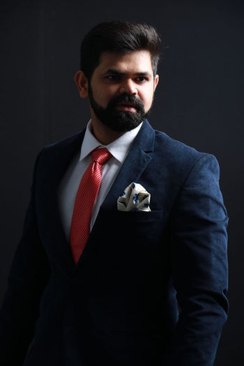 Thoughtful Businessman Wearing Suit While Standing Against Black Background