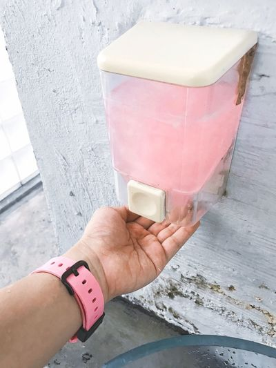 Cropped hand of woman under soap dispenser