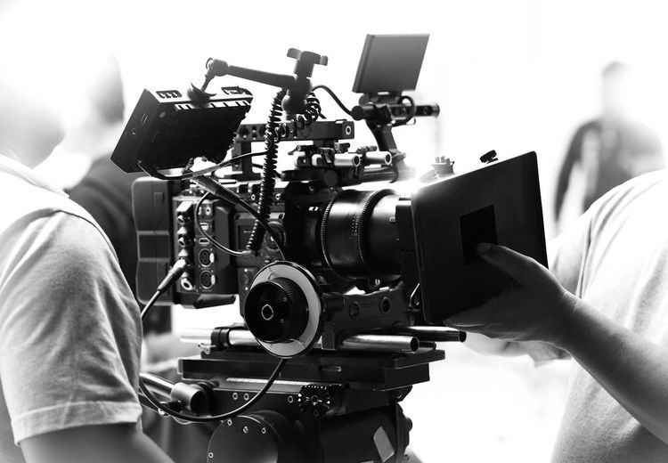 Movie shooting or video filming production by crew team and professional equipment such as super ultra high definition digital camera with tripod and lighting set in studio and black and white styles. Arts Culture And Entertainment Camera - Photographic Equipment Camera Operator Communication Equipment Film Industry Filming Finger Focus On Foreground Hand Holding Human Body Part Human Hand Men Occupation One Person Photography Themes Real People Technology Television Camera Video