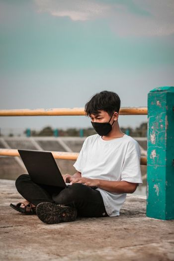 Young man using laptop wearing flu mask sitting by railing outdoors against sky