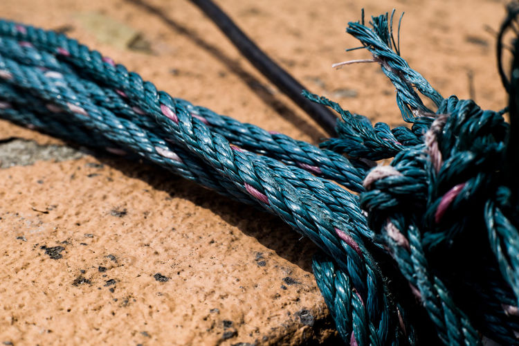 Close-up of rope tied on concrete