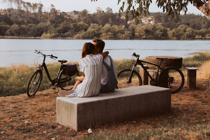 Rear view of couple sitting by lake