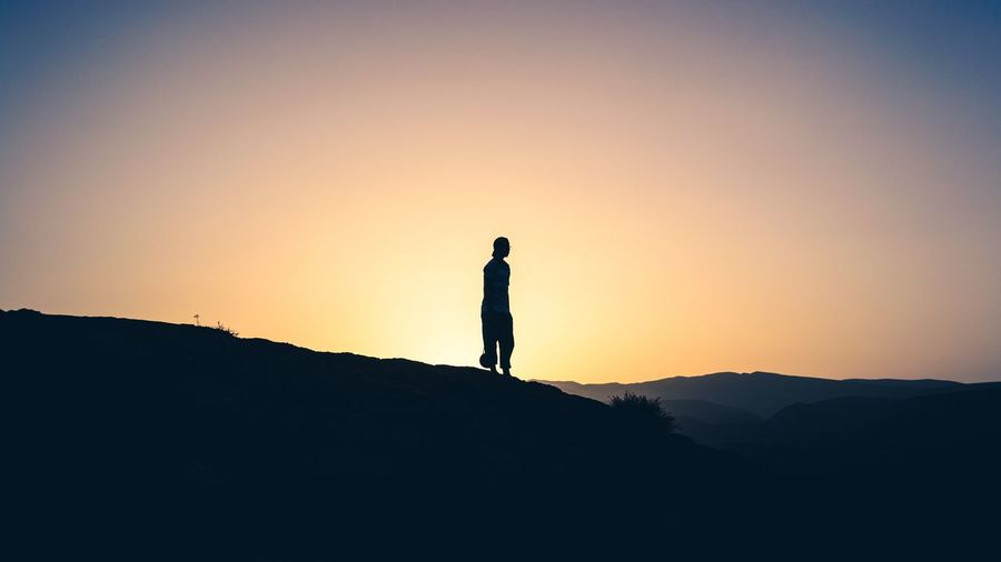 Silhouette man standing on mountain against clear sky