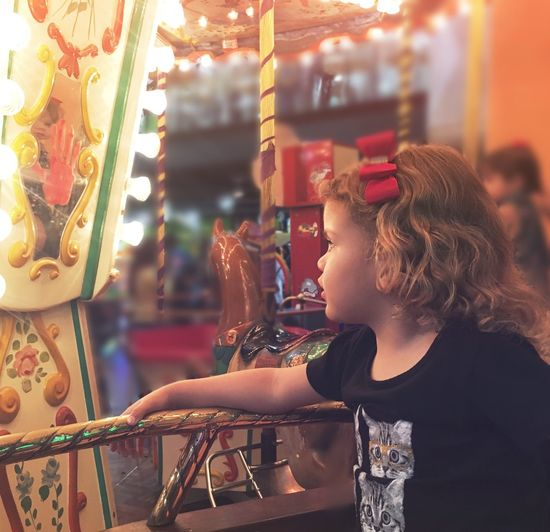 Close-up of girl with carousel in amusement park