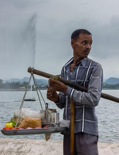 Man holding ice cream against sea