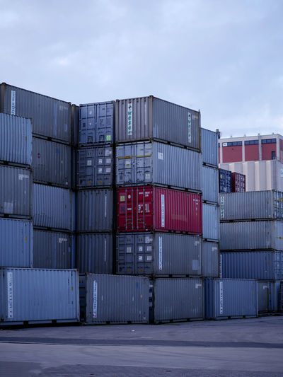 Stack of cargo containers at commercial dock against sky