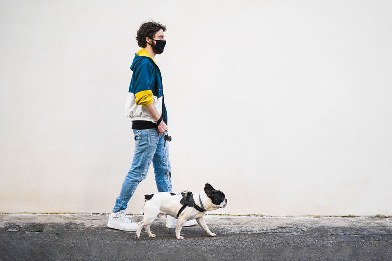 Side view of hipster young man with safety mask with dog standing against wall