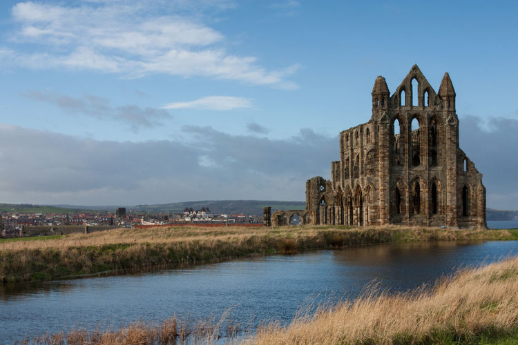 The old Whitby Abbey, Whitby, North Yorkshire with a lake in the foreground and the town in the background. Built Structure Architecture The Past History Sky Building Exterior Building Grass Nature Day Old Cloud - Sky Ancient Travel Destinations Old Ruin Water No People Outdoors Ruined Ancient Civilization Abbey Blue Sky Copy Space Place Of Worship