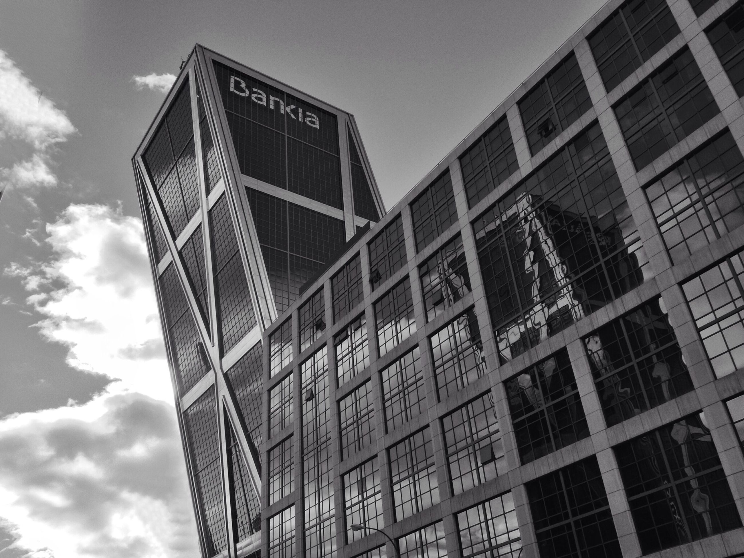 low angle view, architecture, built structure, building exterior, sky, building, modern, glass - material, cloud - sky, window, office building, reflection, day, tall - high, city, tower, outdoors, cloud, no people, pattern