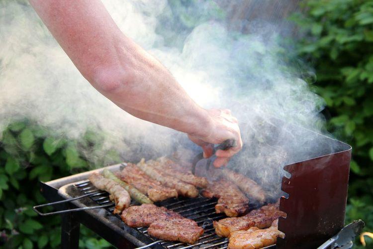 Man preparing food on barbecue grill in yard