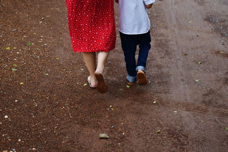 Low section of woman and boy walking on street
