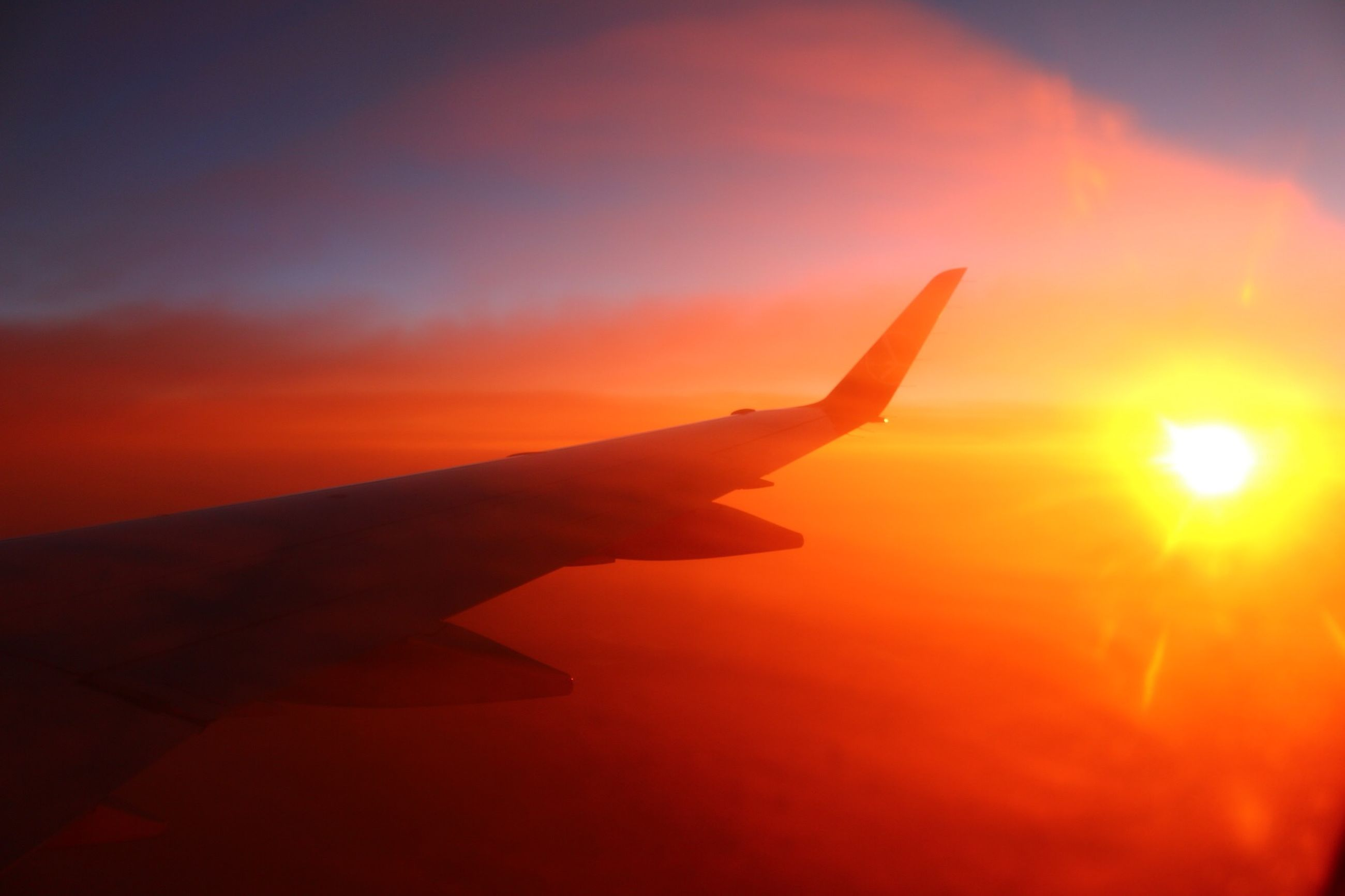 sunset, sun, orange color, part of, sky, flying, person, cropped, silhouette, airplane, sunlight, one person, human finger, cloud - sky, mid-air, aircraft wing, sunbeam, beauty in nature, nature, cloud