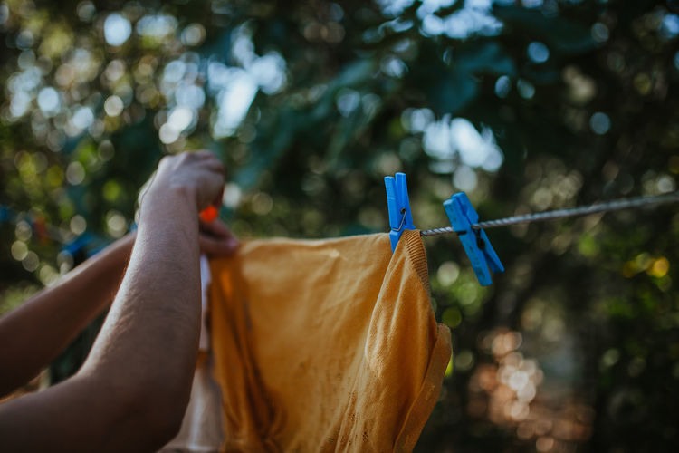 Cropped hand of woman drying clothes on clothesline