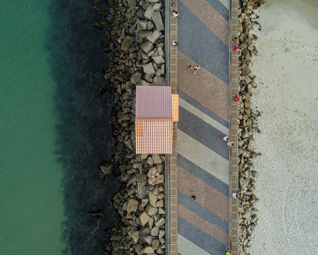 Aerial view of people waking on pier by sea