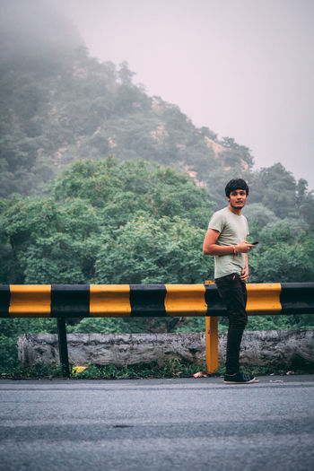 Full length portrait of young man standing against mountain on road