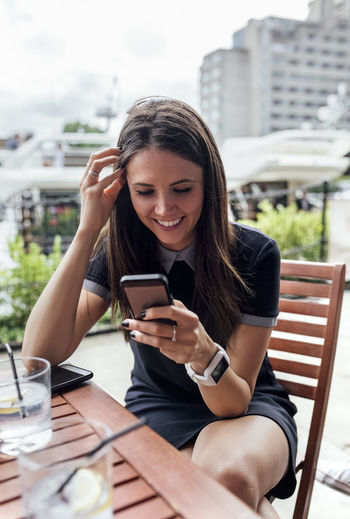 Young woman using mobile phone in restaurant