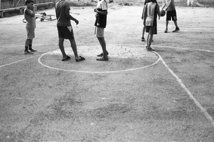 Low section of people playing with ball