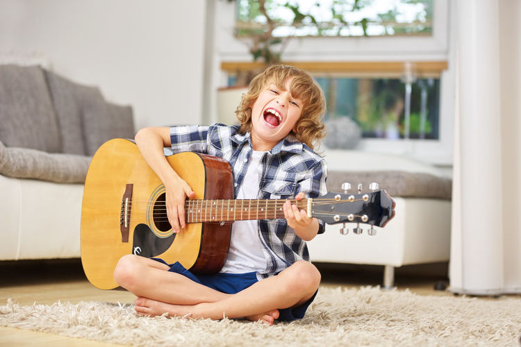 Portrait of cheerful boy playing guitar at home
