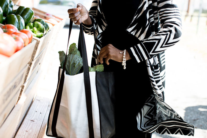 Midsection Of Woman Holding Bag While Standing At Market Stall