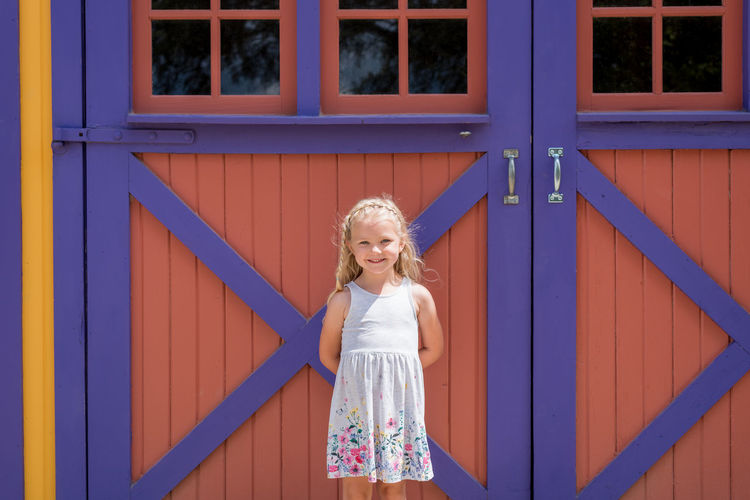 Portrait of smiling girl standing against building