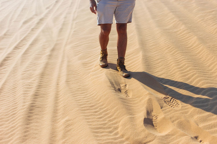 man walking in the desert Copy Space Adult Adults Only Arid Climate Beach Day Desert FootPrint High Angle View Low Section Nature One Person One Woman Only Only Women Outdoors People Sand Sand Dune Shadow Vacations Walking Young Adult