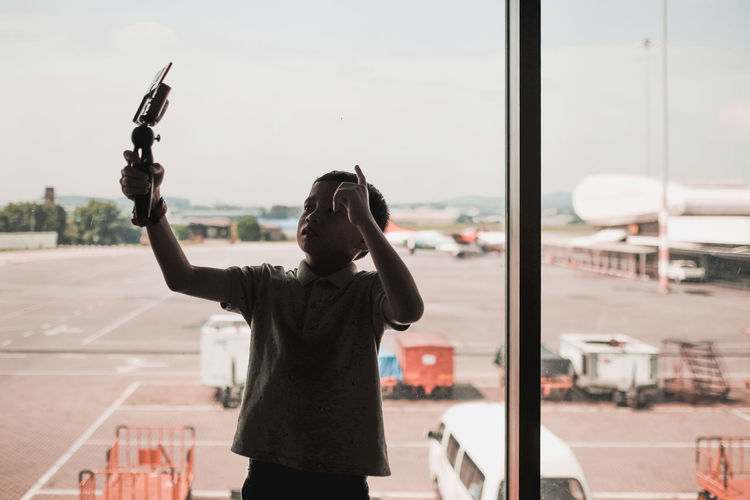 Rear view of man photographing through airplane window